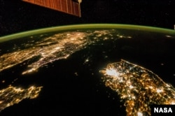 The Korean Peninsula photographed from space, showing the darkness of North Korea in the center of the image, and South Korea at the bottom right.