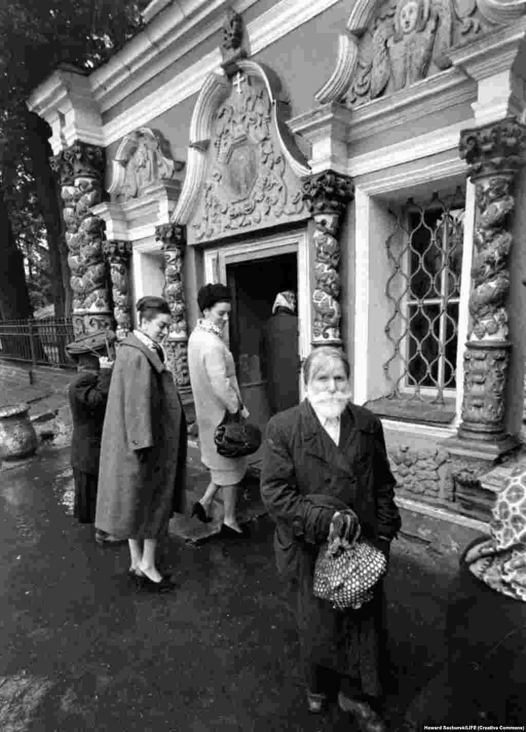 Француженки осматривают советского мужчину при входе в церковь в дождливый день.