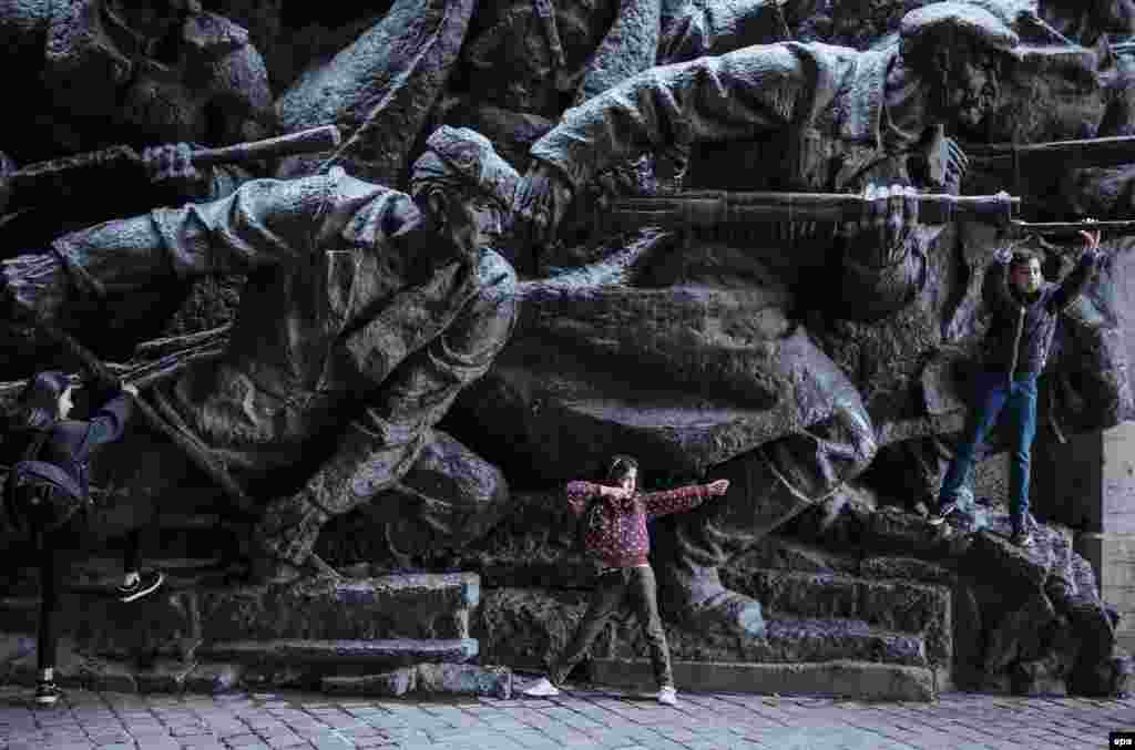 Children play next to the bronze monument at the World War II museum complex in Kyiv, Ukraine. Ukrainians marked the 71st anniversary of the liberation of Ukraine from Nazi occupation during World War II. (epa/Roman Pilipey)
