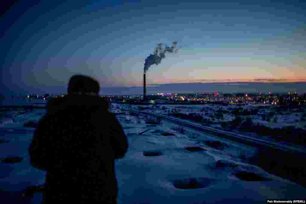 Smoke rises from a chimney over Vorkuta in the evening.
