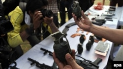 Police officials display arms from suspected criminals in Karachi on March 12, 2014.