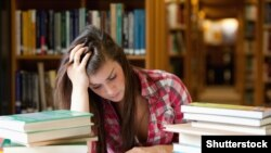 Generic -- (©Shutterstock) Student surrounded by books in a library