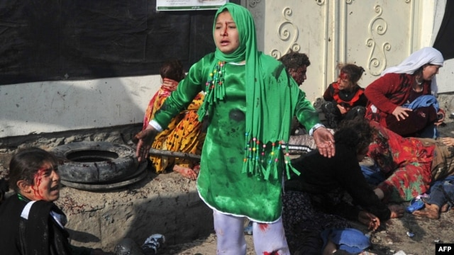 Injured women and young girls cry near the dead and injured from the Kabul explosion.