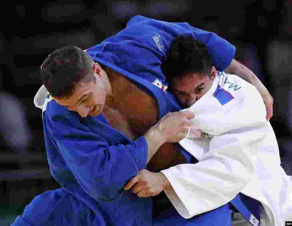 Varlan Liparteliani of Georgia (in blue) and Mashu Baker of Japan clash in the men's 90-kilogram final in judo. Baker, whose father is American, won the gold medal.