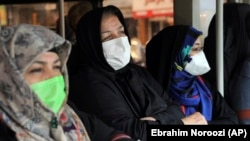 Commuters wear masks to help guard against coronavirus on a public bus in downtown Tehran, February 23, 2020