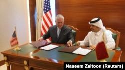 Рекс Тіллерсон (л) і міністр закордонних справ Катару шейх Мухаммад бін Абдаррахман ат-Тані (п) підписують меморандум, Доха, 11 липня 2017 року