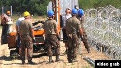 Угорські військові будівельники зводять металевий паркан поруч із загорожею з колючого дроту на кордоні з Сербією