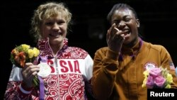 Claressa Shields (right) of the United States poses with her gold medal accompanied by silver medallist Nadezda Torlopova of Russia during the presentation ceremony for the women's middleweight boxing competition at the London Olympic Games on August 9.