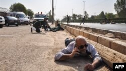 This picture taken on September 22, 2018 in the southwestern Iranian city of Ahvaz shows people and soldiers lying on the ground for cover at the scene of an attack on a military parade.