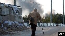 Пожилая женщина проходит мимо КПП по дороге, ведущей в аэропорт Донецка. 2 октября 2014 года.