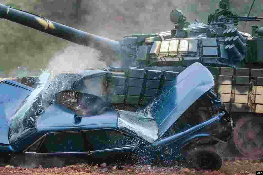 A Belarusian T-72 tank crushes a car during a tank-biathlon competition at the Stalin's Line museum outside Minsk. (AFP/Maksim Malinovsky)
