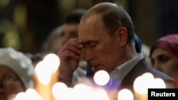 Russian President Vladimir Putin crosses himself as he attends an Orthodox Christmas service at the Holy Face of Christ the Savior Church in the southern Russian city of Sochi early on January 7.