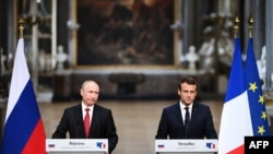France -- French President Emmanuel Macron (R) and Russian President Vladimir Putin look on during a joint press conference following their meeting at the Versailles Palace, near Paris, May 29, 2017