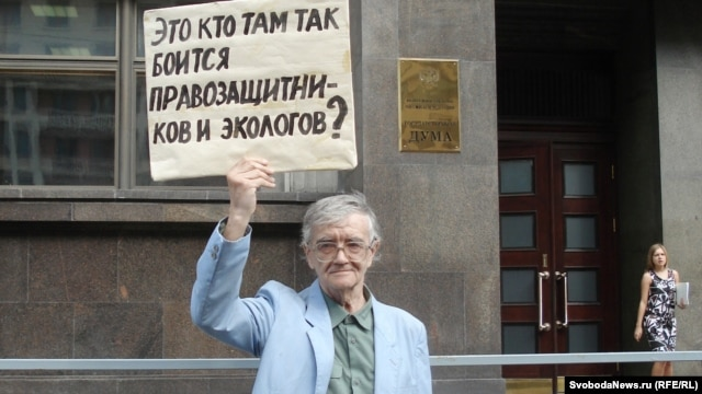 "A supporter of the opposition Yabloko party protests against the NGO bill in front of the State Duma in Moscow on July 6. His sign reads, ""Who is it in there who's so afraid of rights activists and ecologists?"""