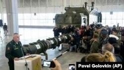 Ракета 9М729, схована в пусковому контейнері, на тлі пускової установки комплексу «Іскандер», для якого вона призначена, на виставці-брифінгу під Москвою, січень 2019 року