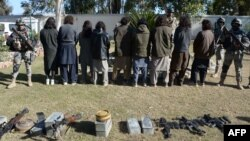 Alleged Taliban militants stand handcuffed near seized weapons in Nangarhar province (file photo).