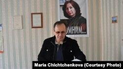 Оюб Тітієв у приміщенні чеченського «Меморіалу» у Грозному на тлі портрету своєї вбитої колеги Наталії Естемірової, архівне фото