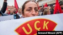 Një grua mban në duar në pankartë me logon e UÇK-së, teksa merr pjesë në një protestë në Prishtinë. 3 nëntor, 2017.