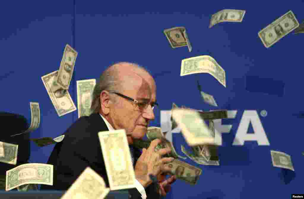 A British comedian, Lee Nelson (not shown), throws banknotes at FIFA President Sepp Blatter as he arrives for a news conference after a FIFA Executive Committee meeting at FIFA headquarters in Zurich. World football's troubled governing body will vote for a new president, to replace Blatter, at a special congress to be held on February 26 in Zurich. (Reuters/Arnd Wiegmann)