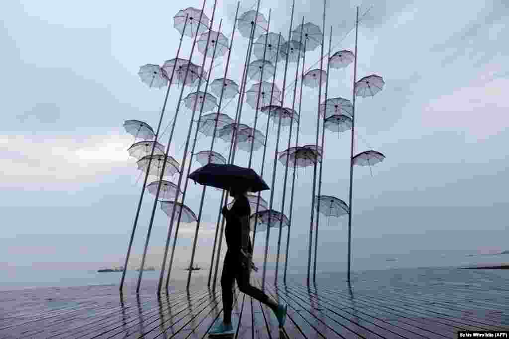 A woman with an umbrella walks past a sculpture called Umbrellas by Greek sculptor George Zongolopoulos, along the waterfront in Thessaloniki. (AFP/Sakis Mitrolidis)