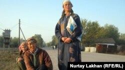 Женщины-репатриантки сидят вдоль дороги в ожидании заказов на поденную работу. Алматинская область, октябрь 2011 года. Иллюстративное фото.