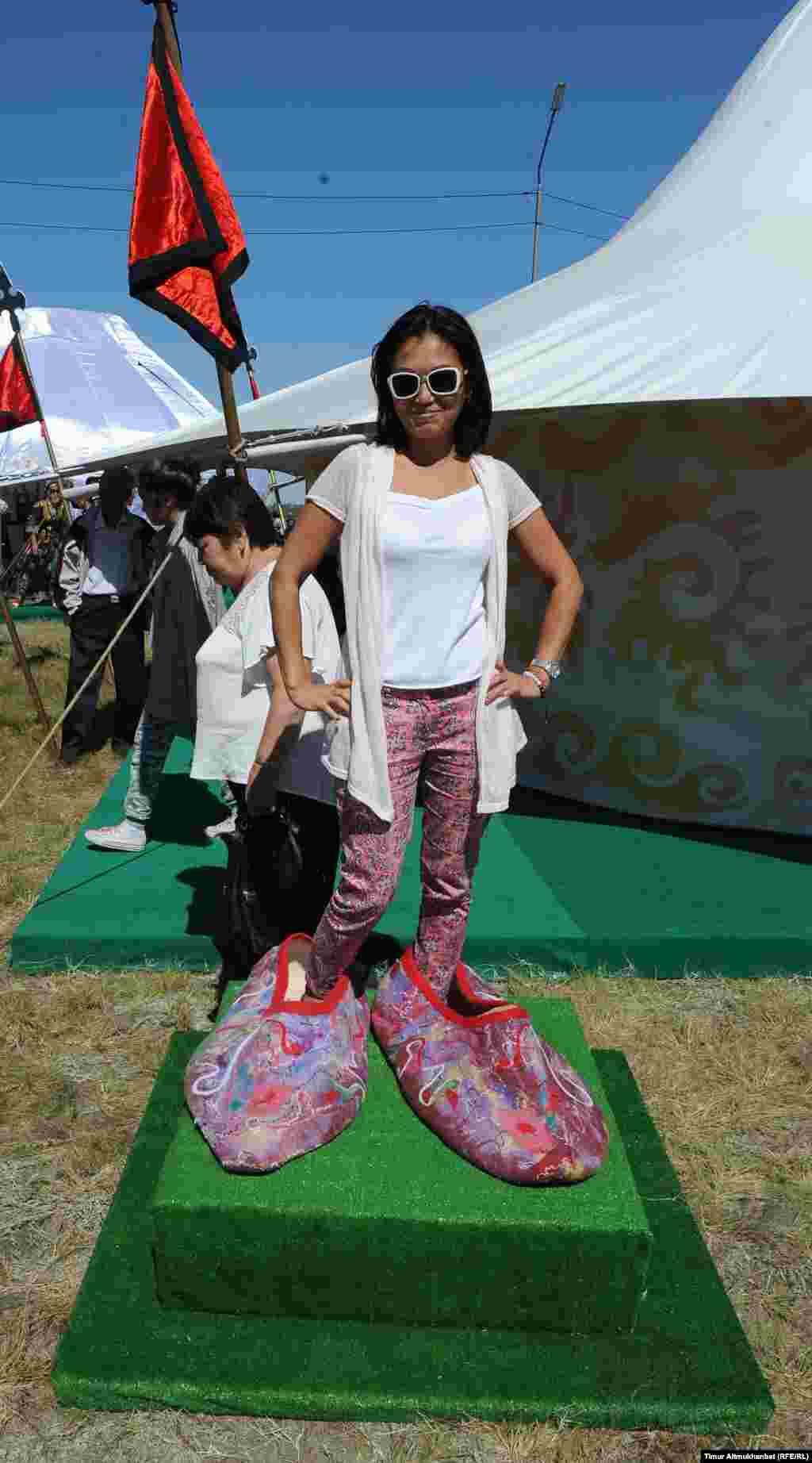 Гостья фестиваля позирует для фото в огромных войлочных бутафорных тапочках.