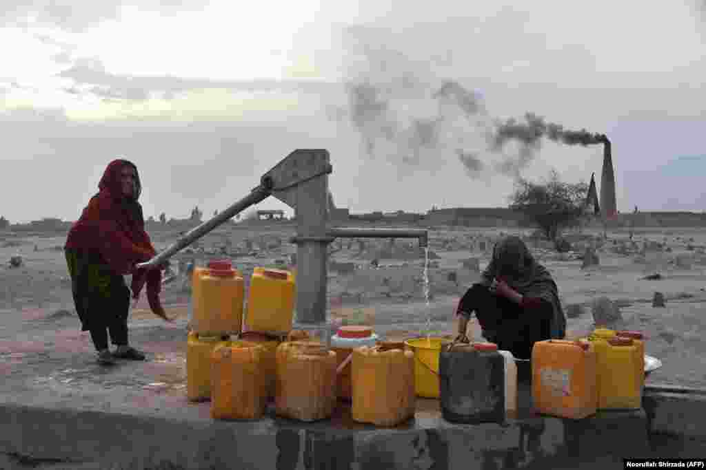 Women collect water from a pump on the outskirts of Jalalabad, Afghanistan. (AFP/Noorullah Shirzada)