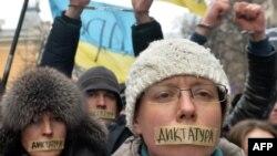 Եվրոպամետ ցուցարարները բերանները փակել են «դիկտատոըւրա» գրությամբ ժապավենով և կանգնել հատուկ ոստիկանության ջոկատի առջև։ Կիև, 17 հունվարի, 2014թ.