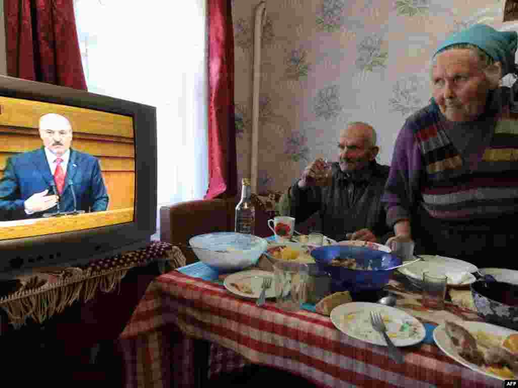 Білоруське подружжя дивиться щорічне звернення президента Олександра Лукашенка, село Рудаков, що у зоні відчуження Чорнобильської АЕС, 21 квітня.Photo by Viktor Drachev for AFP