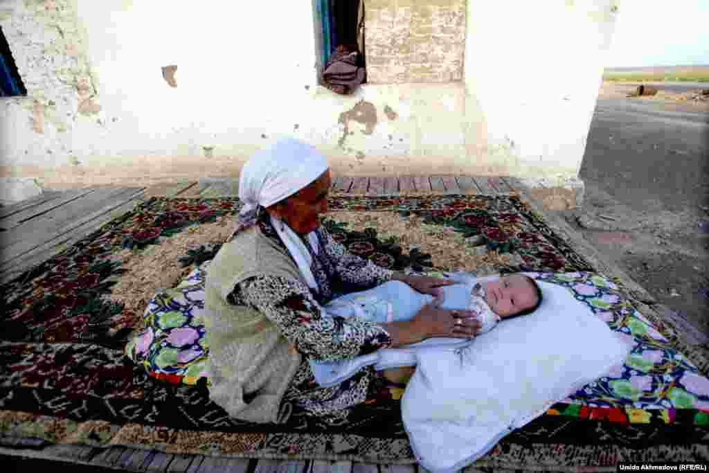 Zhanar's mother-in-law lulls her grandson to sleep.