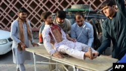 Volunteers carry an injured man on a stretcher to a hospital following the suicide bombing in Nangarhar on June 16.