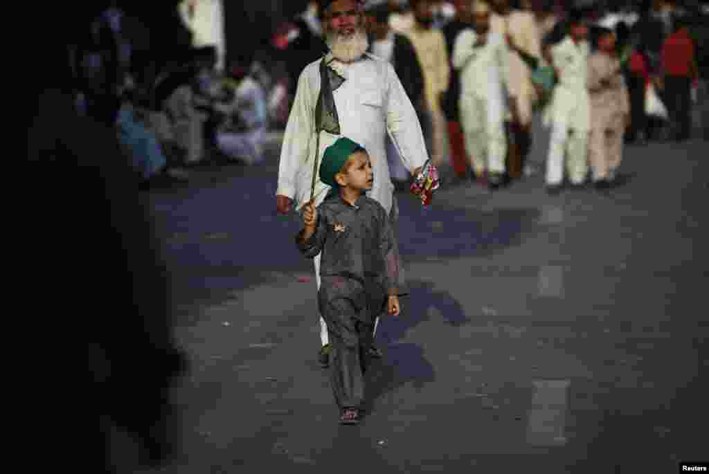 A boy wearing a religious turban carries a flag as he walks along a road during a procession marking Eid-e Milad-ul-Nabi, the birthday celebrations of Prophet Muhammad in Karachi, Pakistan. (Reuters/Akhtar Soomro)