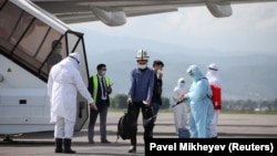 A specialist wearing protective gear sprays disinfectant after the arrival of a plane carrying Kyrgyz citizens from Japan and South Korea in Almaty on May 14.