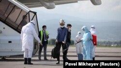 Атайын рейс менен Түштүк Кореядан келген кыргызстандыктарды Алматынын аэропортунда дезинфекциялап жатышат. Казакстан. 14-май, 2020-жыл.