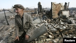 A man sits amid the ruins of his home after the spread of a forest fire from Kazakhstan to the village of Nikolaevka.