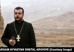 Епископ Топузян со слезами на глазах говорит об уничтожении кладбища. За его спиной — территория Азербайджана, где происходит разрушение исторического памятника. Епископ умер в 2010 году.