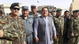 FILE: Abdul Jabar Qahraman surrounded by Afghan military and police officers in Helmand Province.