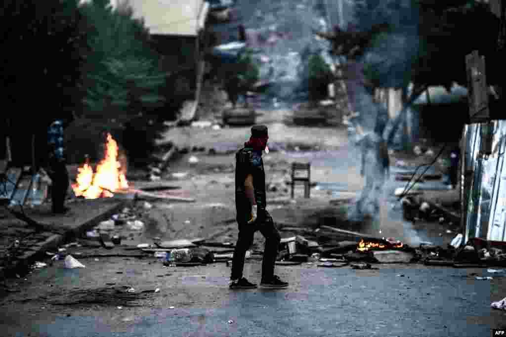 По сообщениям агентства AFP, во время протестов погиб один сотрудник полиции, один мирный житель, несколько десятков человек были задержаны На фото - протестант КРП стоит напротив баррикад в Стамбуле