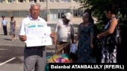 Житель города Жанаозена Хасен Дуйсекенов стоит с плакатом в руках у здания городского акимата с требованием встречи с премьер-министром Каримом Масимовым. Жанаозен, 16 июля 2012 года.
