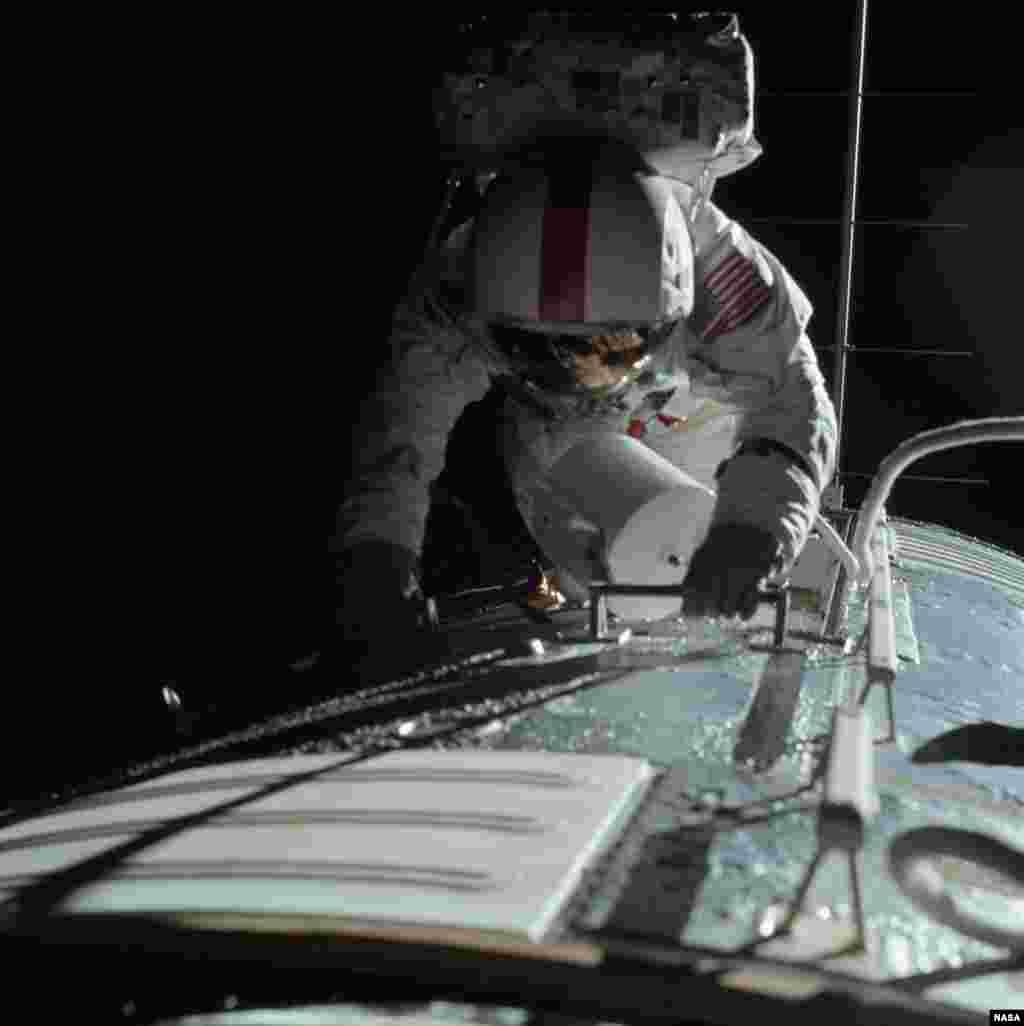 Астронавт Рональд Эванс извлекает пленку из специальной фотокамеры в открытом космосе.