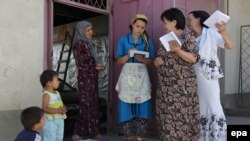 Women discuss the voting before casting their ballot papers at a mobile ballot box in the Uzbek district of Unadir in Osh.