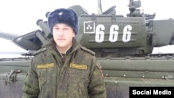 A Russian soldier stands next to a T-72B3 tank with the tactical sign of the 6th Tank Division.