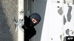 A hooded French policeman looks outside the window on March 23 as he investigates the flat where self-professed Al-Qaeda militant Mohamed Merah, 23, was living in Toulouse.