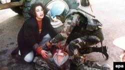 """Fotografija iz opkoljenog Sarajeva, francuski vonik UNPROFOR-a pomaže pogođenima u """"Aleji snajpera"""" 21. novembar 1994."""