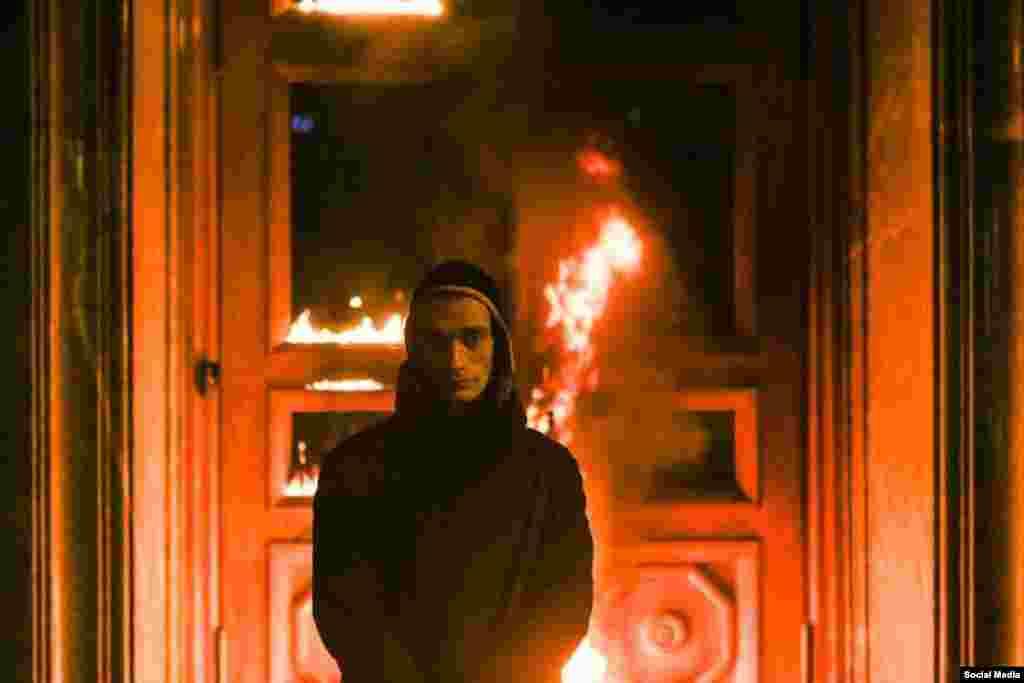 Петр Павленский на фоне горящей двери здания ФСБ на Лубянке в Москве. 9 ноября 2015 года.
