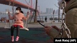Дівчинка в масці грається біля мосту Ін'ючжоу через річку Янцзи в місті Ухань, 29 січня 2020 року