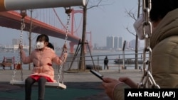 A girl wears a face mask as she plays on a swing in Wuhan, China, where the virus was first identified.