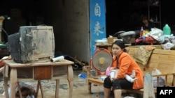 Женщина, пострадавшая от наводнения, сидит возле своего разрушенного дома. Китай, 19 сентября 2011 года.