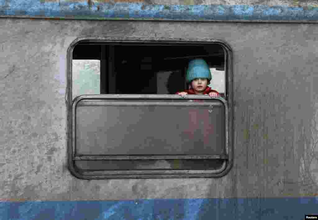 A migrant child looks out of a window at a train station in the town of Sid, Serbia. (Reuters/Marko Djurica)
