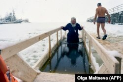 A Russian Orthodox priest takes an Epiphany dip in the icy waters of the Gulf of Finland outside St. Petersburg.